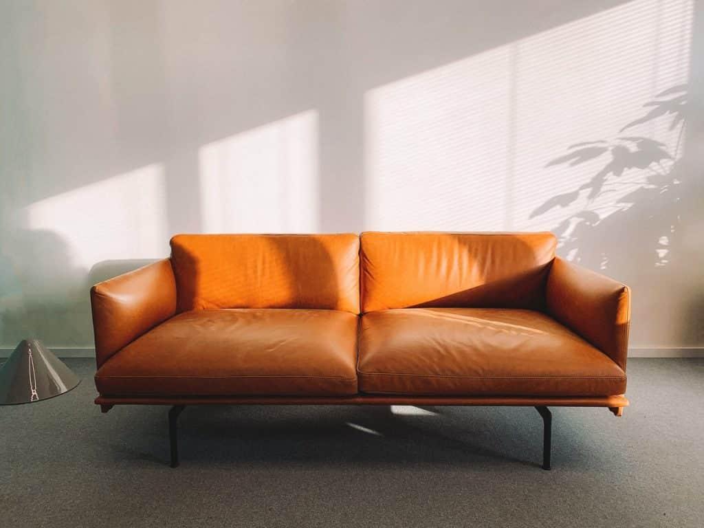 Sala de estar com sofá ao lado de uma janela.