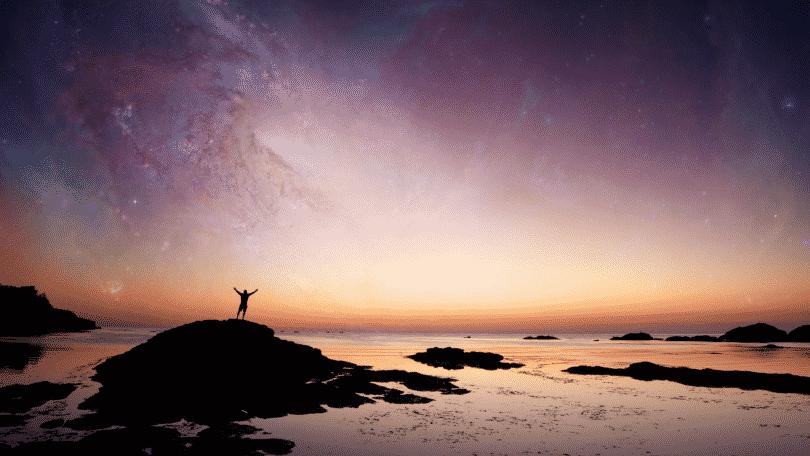 Pessoa com os braços erguidos na praia contemplando o universo
