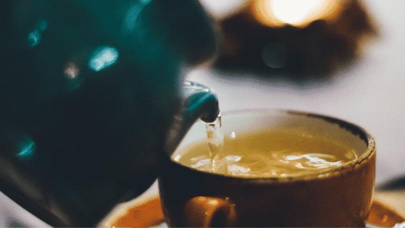 Bule colocando chá na xícara