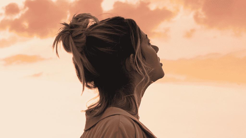 Mulher olhando para o céu pensativa