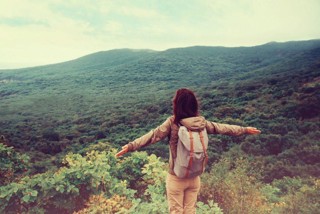 Mulher de costas com braços aberto em montanha com paisagem de natureza
