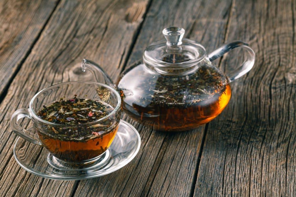 Chá em uma xícara e em um bule com ervas