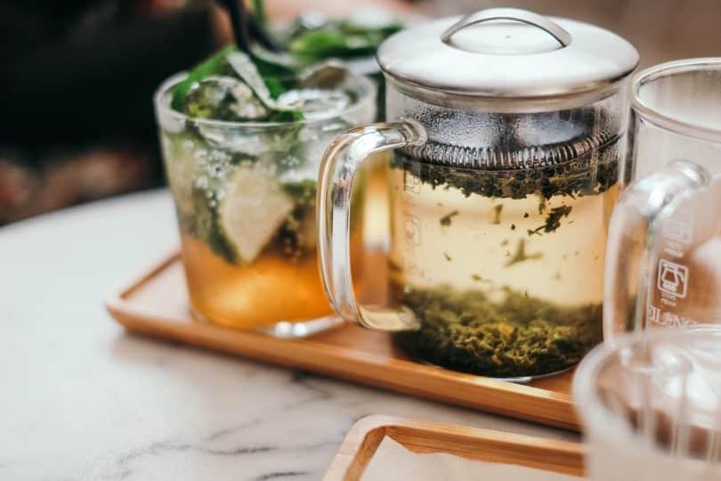 Bule com chá e xícara com chá um ao lado do outro
