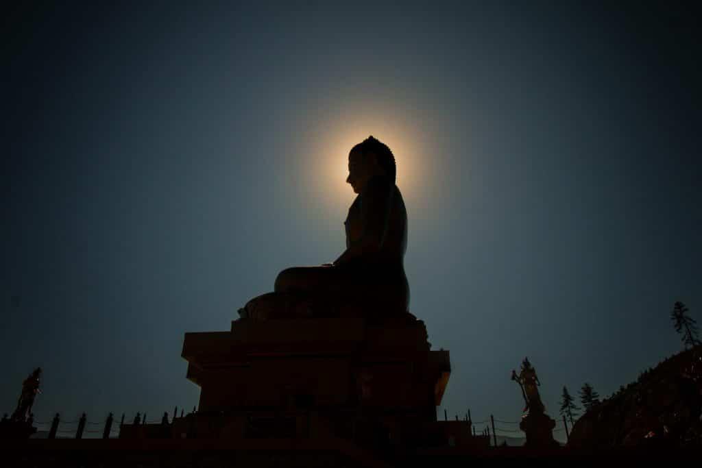 Silhueta de uma estátua de buda sentado em pose de meditação.