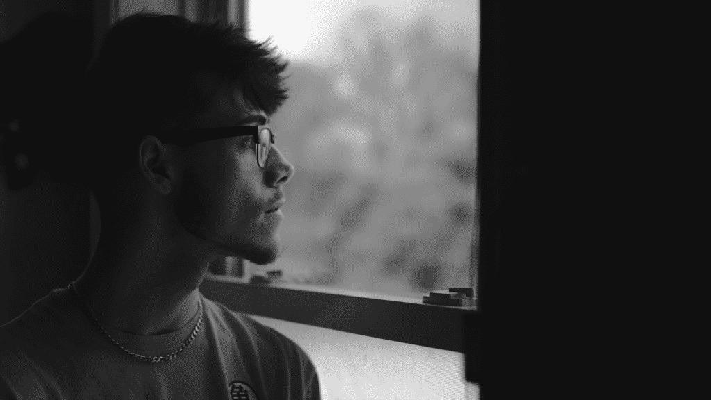 Homem olhando pensativo pela janela