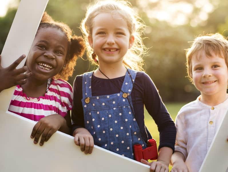 Três crianças sorrindo enquanto brincam em um parque
