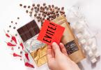 Foto de chocolates, grãos de café e cubos de açúcar dispostos em uma mesa. Acima desses alimentos há uma mão segurando um post-it vermelho escrito 'evite'.