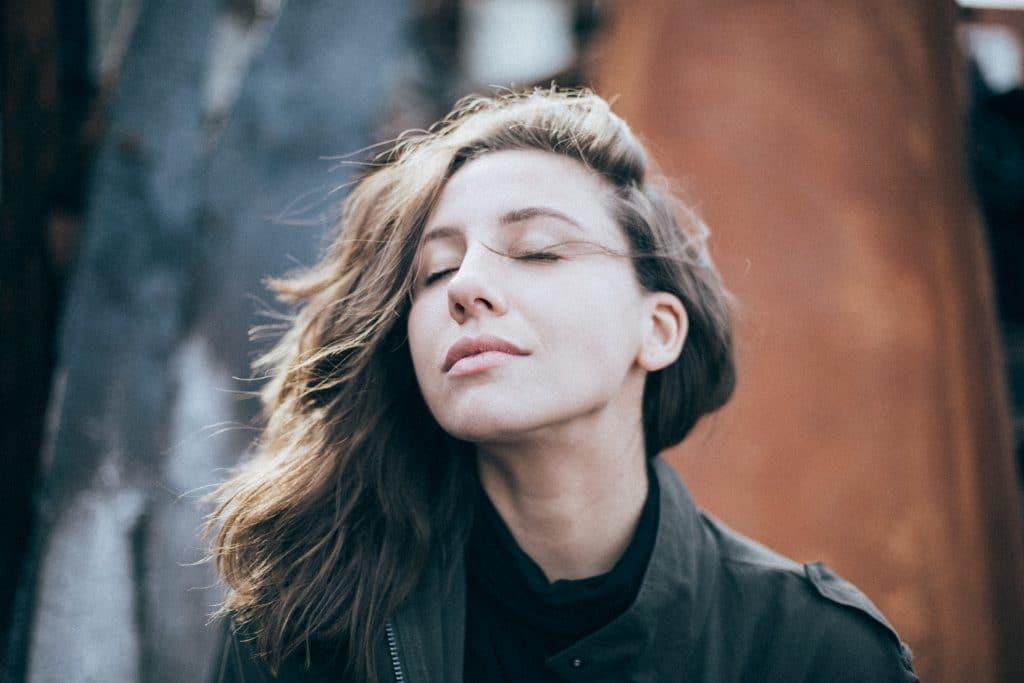Mulher de olhos fechados respirando fundo.
