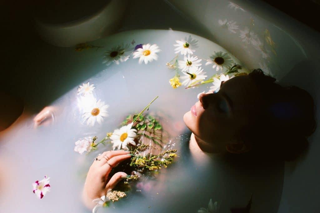 Mulher em uma banheira com flores e ervas.