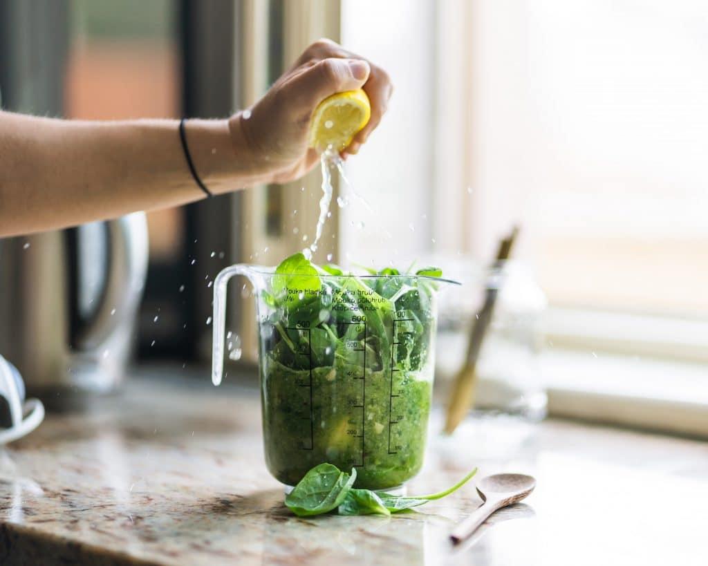 Pessoa espremendo um limão em uma vitamina verde, com folhas de espinafre.
