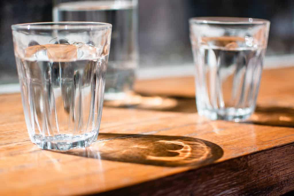 Dois copos de água sobre uma mesa de madeira.