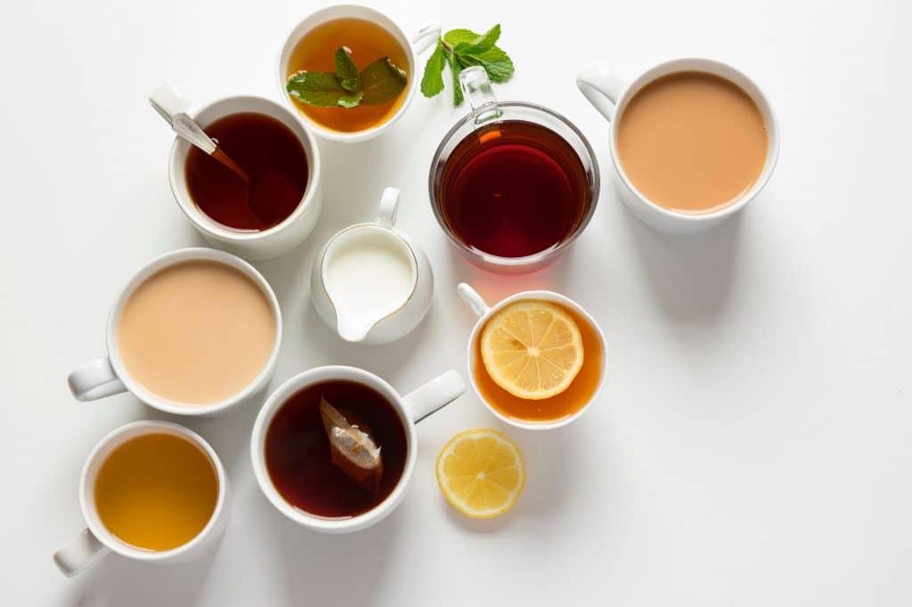 Várias xícaras com tipos diferentes de chás sobre uma mesa.