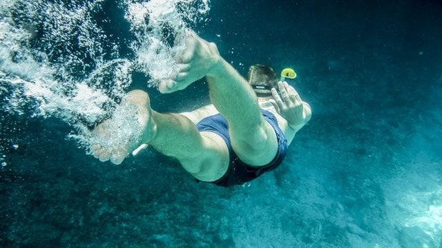 Homem nadando com sunga e óculos de natação.
