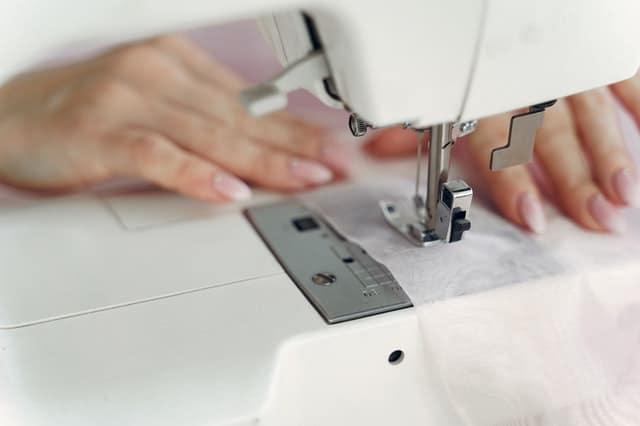 Detalhe de máquina de costura, sendo manuseada pelas mãos de uma mulher.