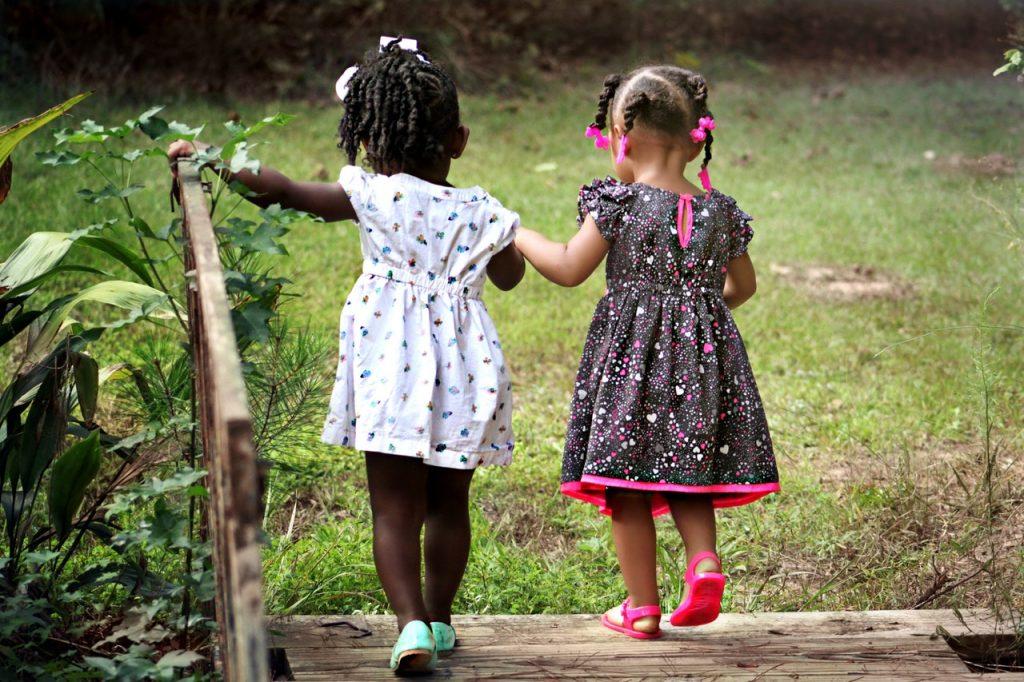 Duas meninas crianças caminhando de mãos dadas por um parque.