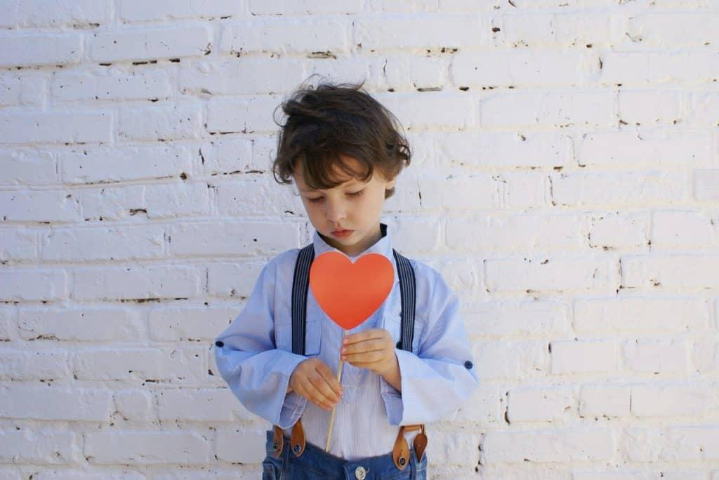 Menino segurando um palito com um coração de papel colado ao topo.