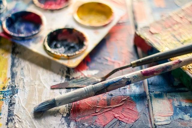 Pincel e espátula sujos de tinta, ao lado de uma paleta, sobre uma mesa de madeira suja com tintas diferentes.