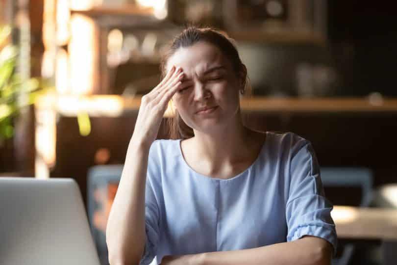 Mulher com dor de cabeça e mão na testa