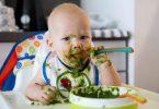 Bebê comendo sozinho com o rostinho cheio de comida