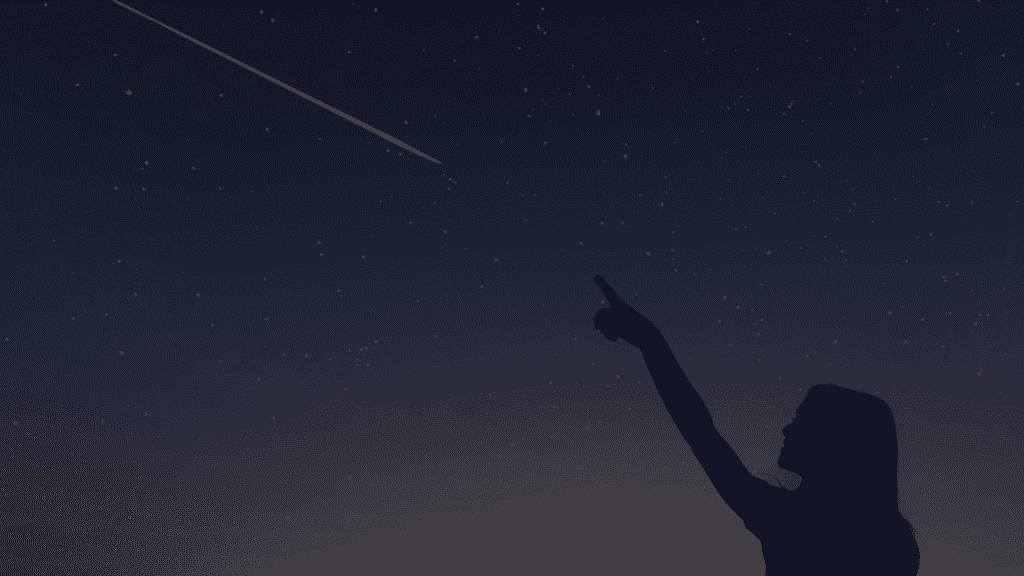 Criança apontando para uma estrela cadente