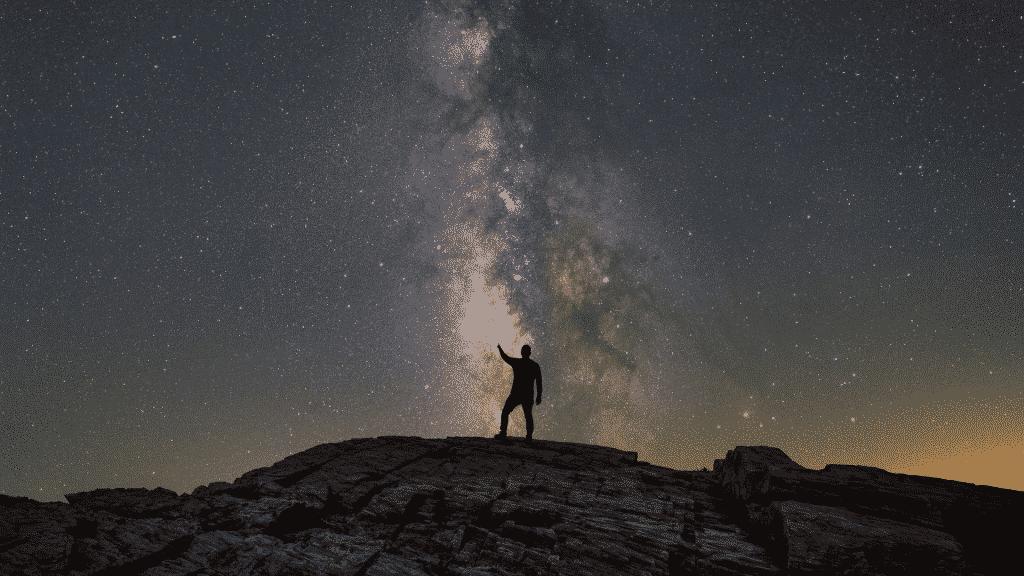 Silhueta de um homem apontado para as estrelas