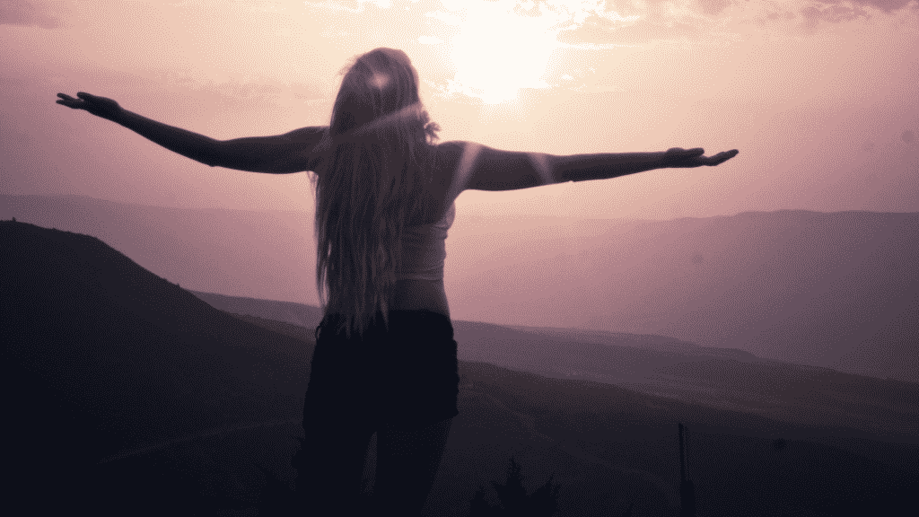 garota de costas com de braços abertos encarando o horizonte sob uma montanha