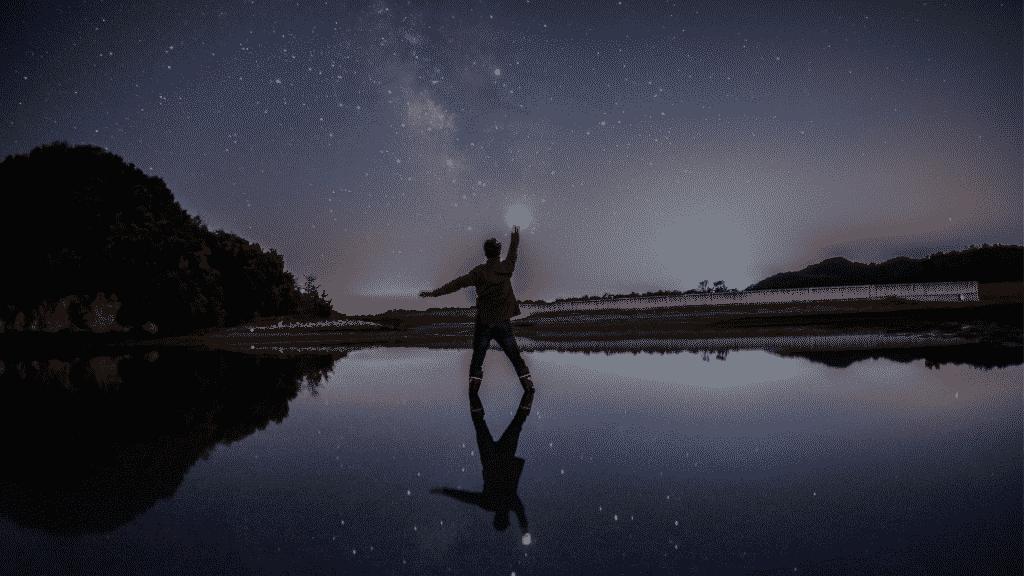 Silhueta de garoto na noite com o braço estendido que cria a ilusão que ele está tocando na estrela do céu