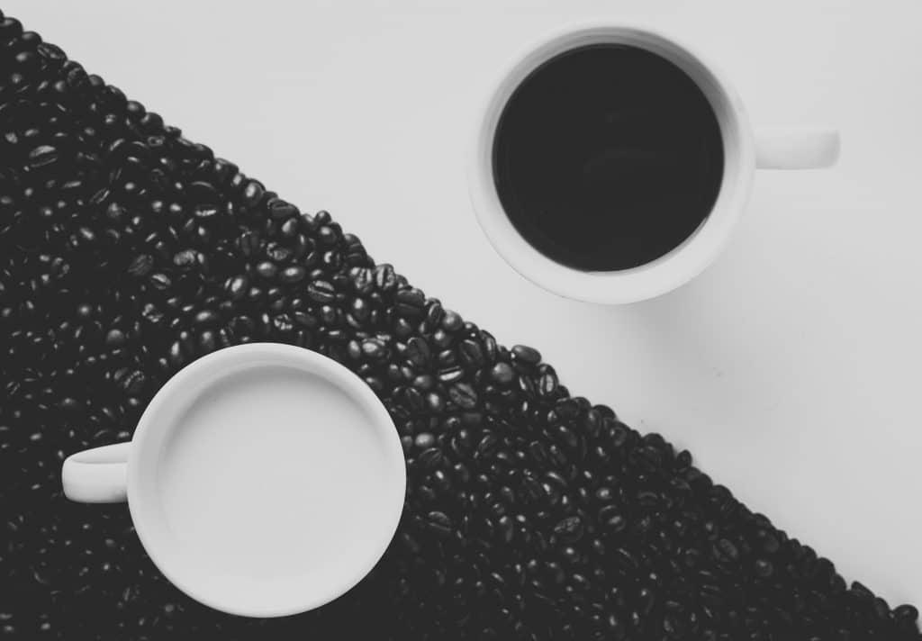 Xícara com café em uma superfície branca.