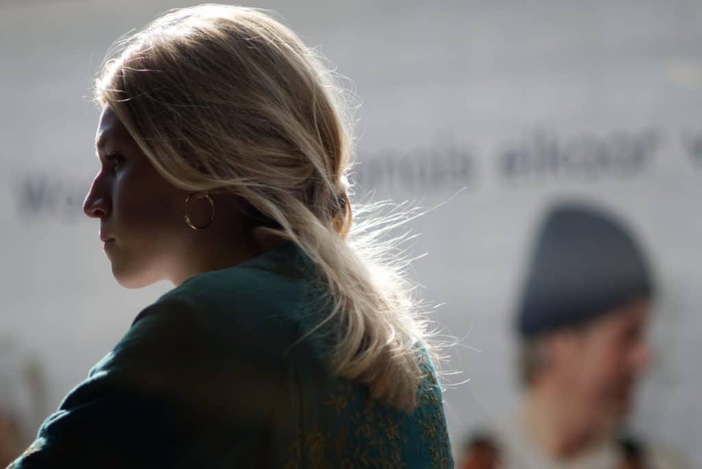 Mulher loira sentada olhando para o horizonte com um semblante de tensão.