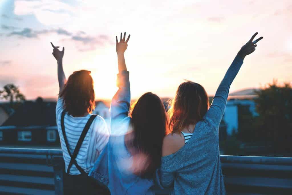 Três mulheres com os braços levantados olhando para o sol
