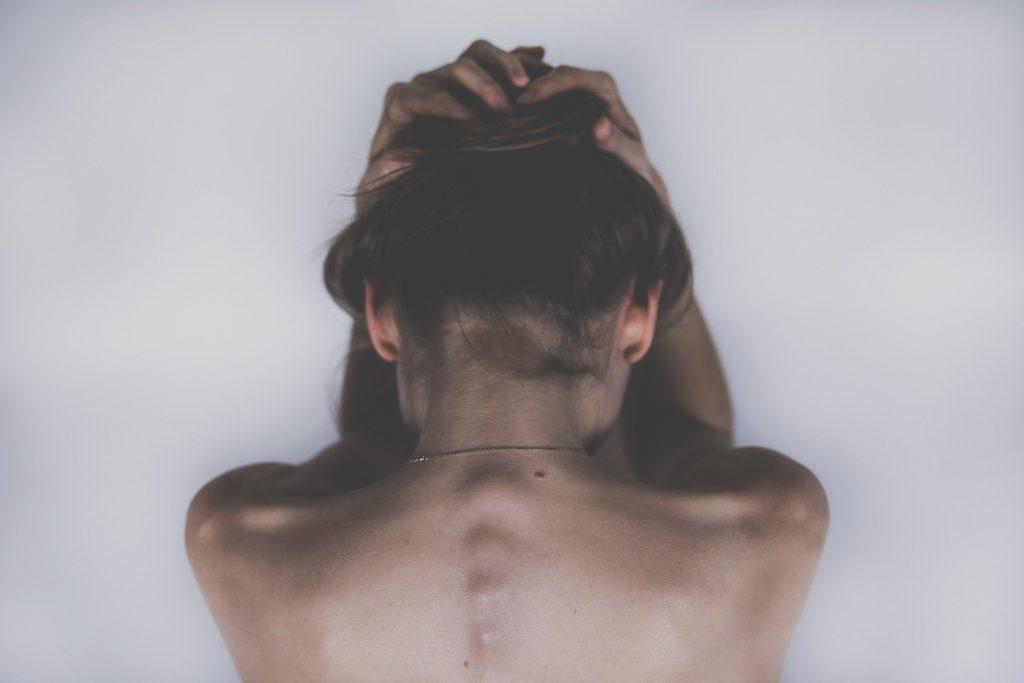 Mulher de costas com a cabeça baixa e as mãos na cabeça.