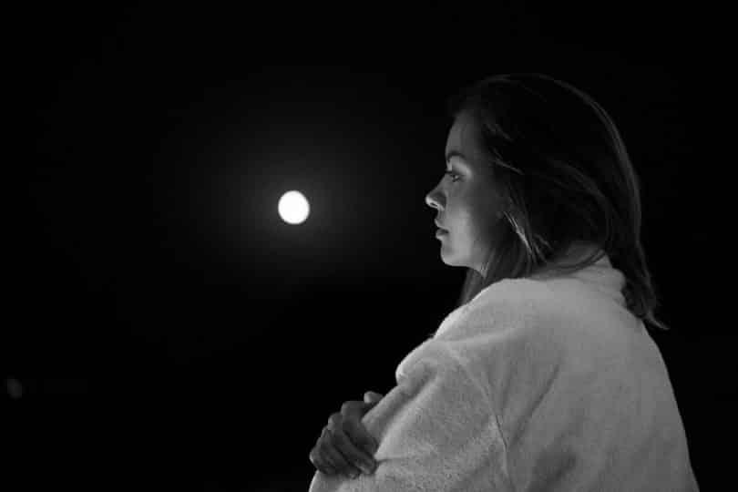 Jovem olhando para a lua cheia