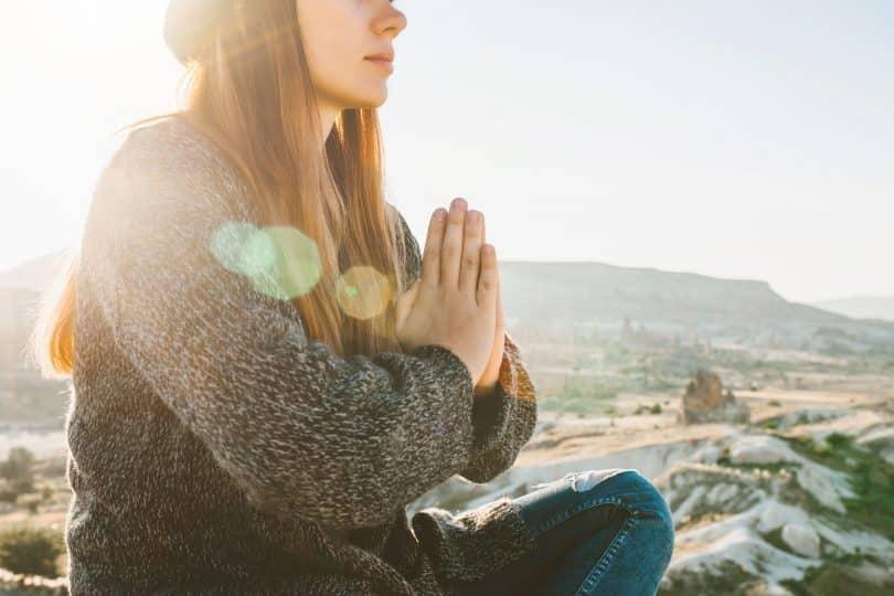 Mulher branca sentada numa pedra com as mãos juntas.