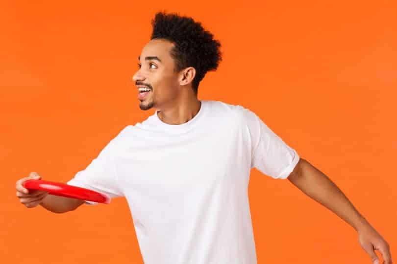 Homem negro usando camiseta branca, jogando disco vermelho.
