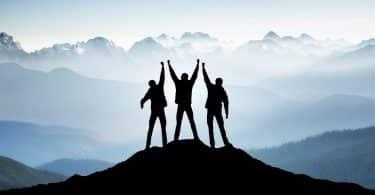 Três pessoas no topo da montanha com os braços levantados