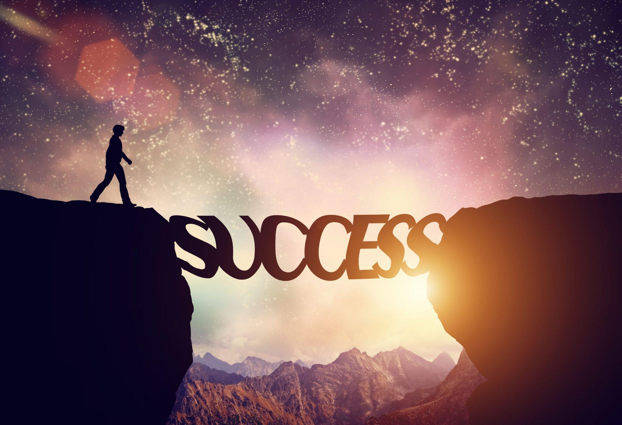 """Pessoa andando em uma montanha e em sua frente a palavra """"sucesso"""" para ele caminhar e atravessar a ponte"""