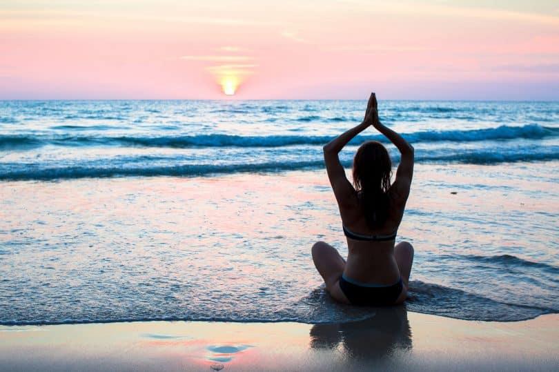 Mulher de costas meditando na praia.