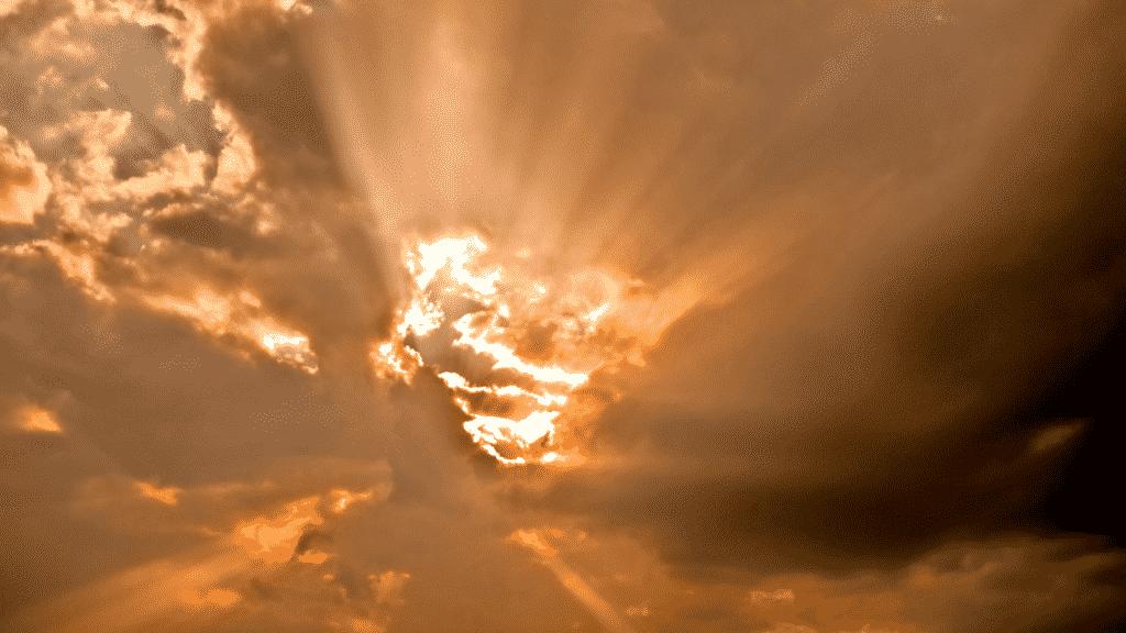 Imagem do céu alaranjado coberto de nuvens com alguns feixes de sol entre elas