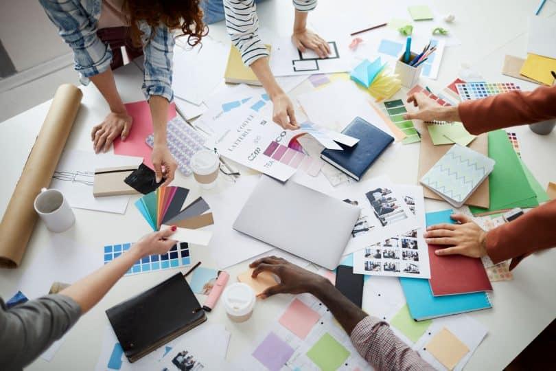 Mesa com cadernos e papéis coloridos.