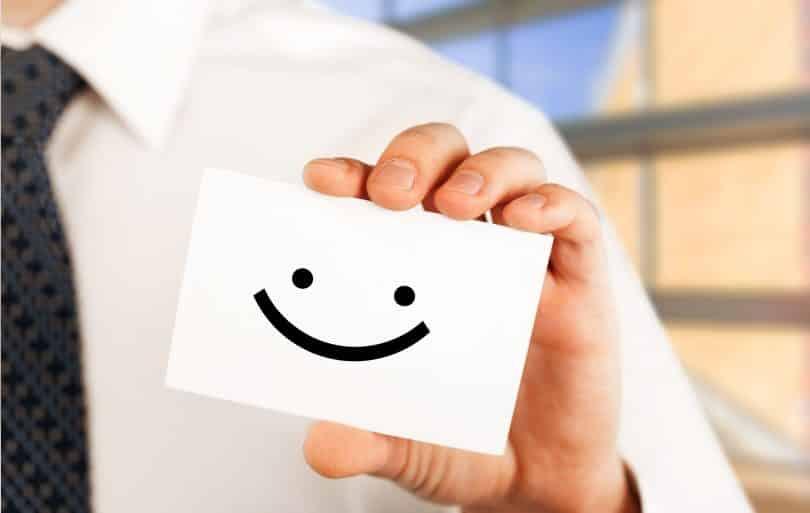 Homem vestindo camisa e gravata segura um papel branco com desenho de sorriso.