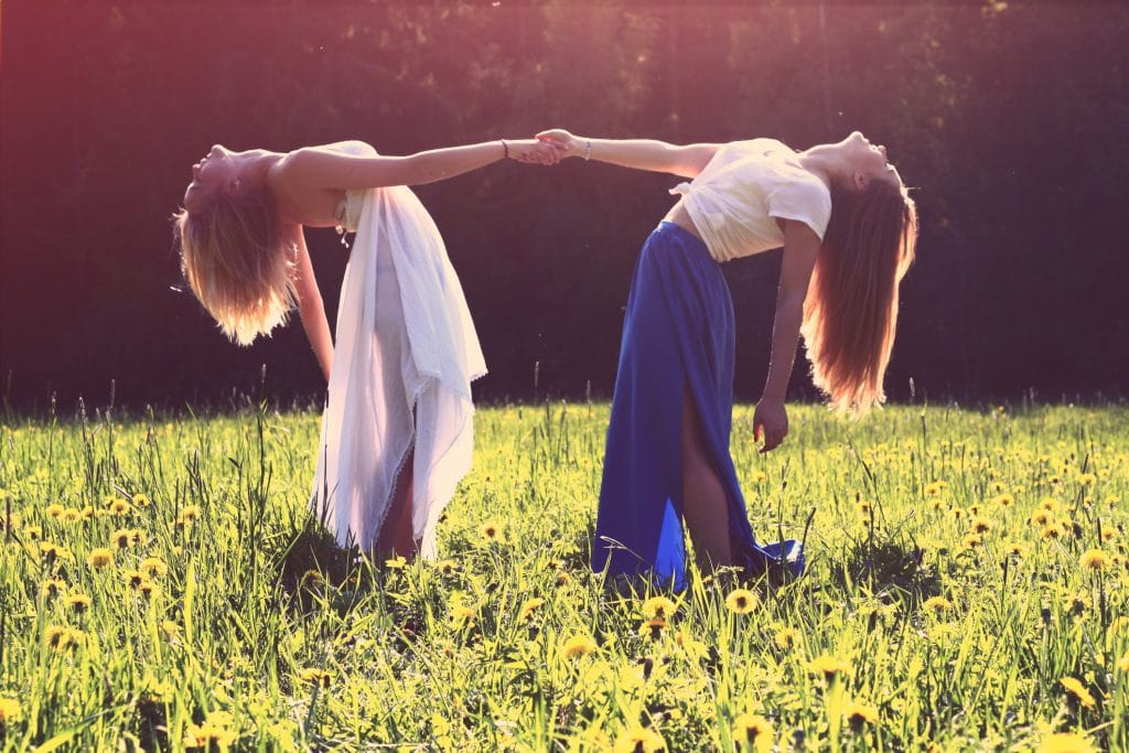 Duas mulheres de mãos dadas jogando os corpos para trás.