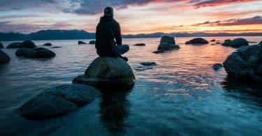 Homem sentado em uma rocha em um mar, olhando para o céu