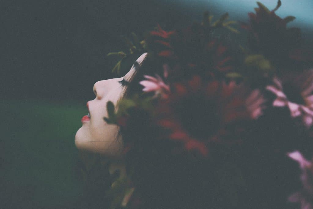 Moça asiática com flores no cabelo.