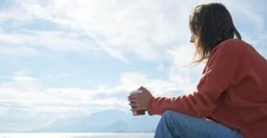 Mulher sentada na praia segurando copo de café