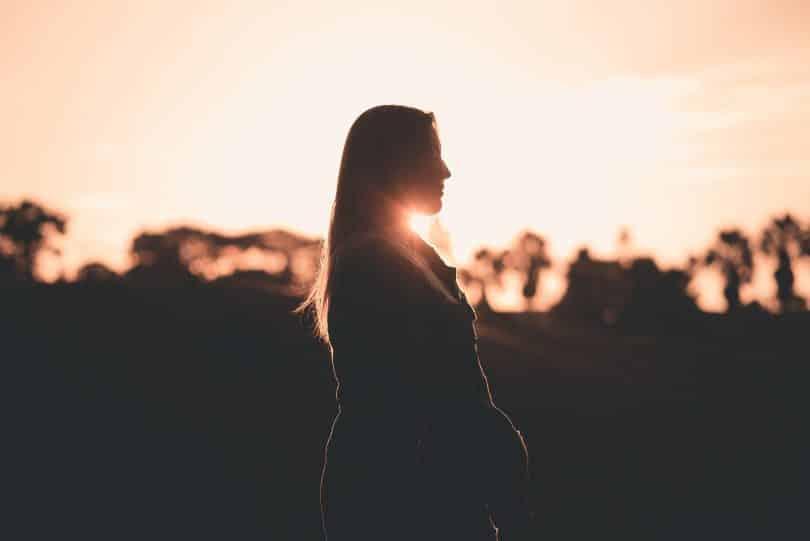 Mulher de olhos fechados sendo iluminada pelo pôr do sol