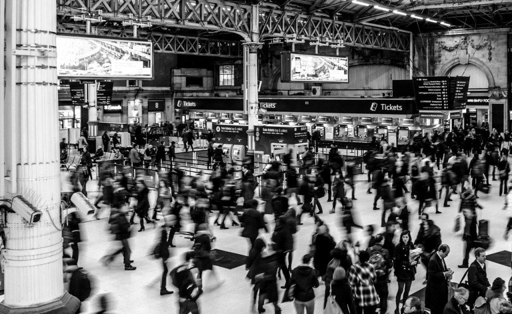 Várias pessoas andando apressadamente em uma estação de trem