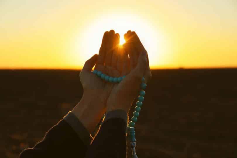 Recorte de uma mão orando com o pôr do sol ao fundo.