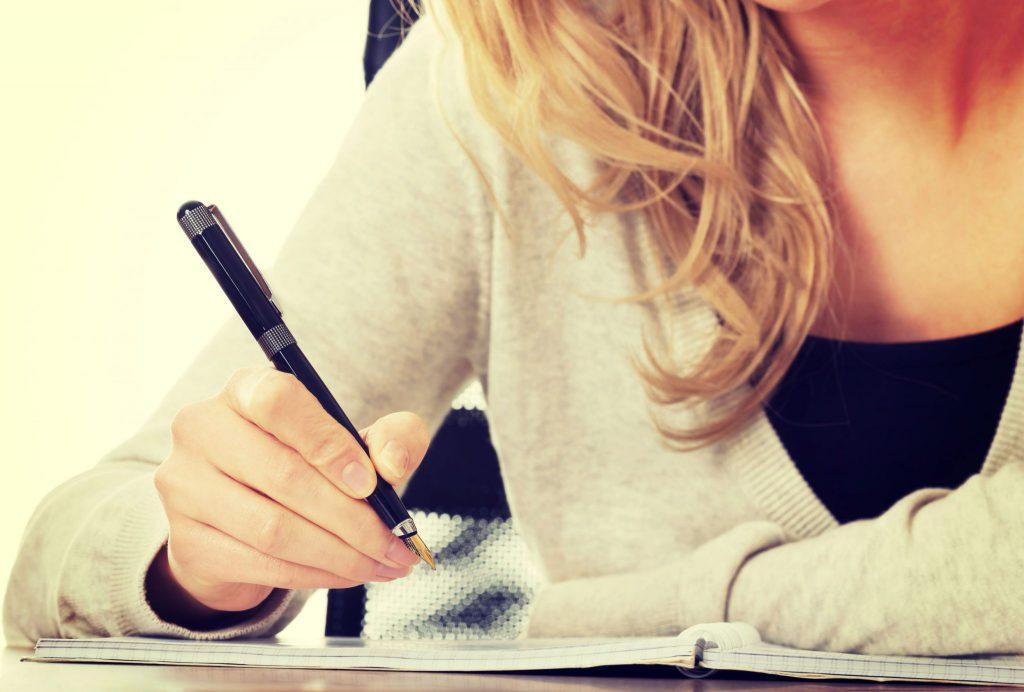 Mulher segurando caneta, prestes a escrever em um caderno.
