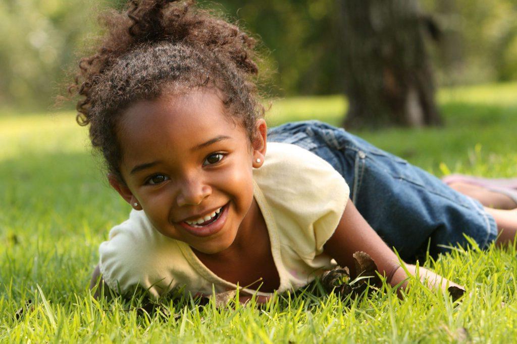 Menina pequena deitada de bruços na grama, sorrindo para a câmera.