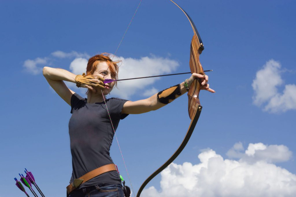 Mulher jovem segurando arco, prestes a soltar uma flecha.